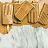 Flatlay of melting coffee latte popsicles, square crop. Summer healthy vegan frozen dessert. Flatlay of melting coffee latte popsicles over light grey marble stock photo
