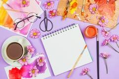 Flatlay met kunstlevering, kunstenaarspalet, glazen, bloemen, kop thee en sketchbook met blanco pagina Stock Fotografie