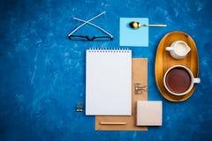 Flatlay Modell des stilvollen Geschäfts mit Notizbuch, Gläsern, Bleistift, Milchhalter und Tee auf hölzernem Behälter stockfoto