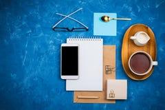 Flatlay Modell des stilvollen Geschäfts mit Notizbuch, Gläsern, Bleistift, Milchhalter und Tee auf hölzernem Behälter und Smartph stockfoto