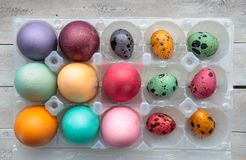 Flatlay multicolored Easter eggs in the package colorfull quail eggs. Multicolored Easter eggs in the package colorfull quail eggs cards Stock Image