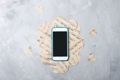 Flatlay music composition smartphone or mobile phone, paper hear. Ts on gray concrete background Royalty Free Stock Images