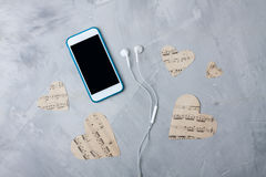 Flatlay music composition smartphone or mobile phone, paper hear. Flatlay composition smartphone or mobile phone, paper hearts, headphones on gray concrete Royalty Free Stock Photo