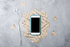 Flatlay music composition smartphone or mobile phone, paper hear. Ts, headphones on gray concrete Stock Photos