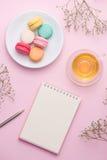Flatlay notatnik, tortowy macaron, filiżanka herbata i kwiat na menchiach, Obrazy Royalty Free