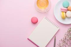 Flatlay notatnik, tortowy macaron, filiżanka herbata i kwiat na menchiach, Zdjęcia Royalty Free