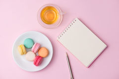 Flatlay of notebook, cake macaron and cup of tea on pink table. Beautiful breakfast with macaroon Stock Image
