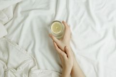 Free Flatlay Of Woman`s Hands Holding Glass In Lemon Water In Bed On White Sheets Stock Photo - 124716920