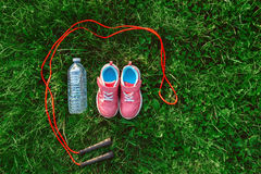 Flatlay with pair of pink girl sneakers shoes, jump rope and bottle of water in green grass Stock Photos
