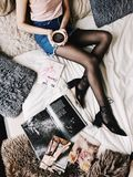 Flatlay Photography of a Woman Holding White Mug With Black Liquid While Lying on a Bed Surrounded by Fur Pillows and Magazines Stock Image