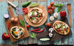 Flatlay of pizza party. Homemade pizzas and raw vegetables in ab. Undance on oak chopping boards over shabby blue wooden background overhead view royalty free stock images