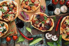 Flatlay of pizza party. Pizzas in abundance with raw vegetables,. Salami, mushrooms and red wine on dark oak chopping boards over blue rustic background Royalty Free Stock Image