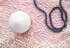 Flatlay roze achtergrond, bevallig wit duur kant en elegante zwarte parel met kaars, romantische stijl stock afbeeldingen