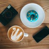 Flatlay sammansättning med telefonen, kaffe, kamera, munk på trätabellen royaltyfri bild