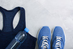 Flatlay sport composition with outfit blue sneakers and t-shirt. Flatlay sport composition with blue sneakers, t-shirt and bottle of water on gray concrete Royalty Free Stock Photo