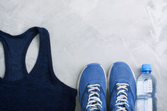 Flatlay sport composition with outfit blue sneakers and t-shirt. Flatlay sport composition with blue sneakers, t-shirt and bottle of water on gray concrete Royalty Free Stock Images