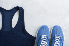 Flatlay sport composition with outfit blue sneakers and t-shirt. Flatlay sport composition with blue sneakers and t-shirt on gray concrete background. Concept Royalty Free Stock Photo