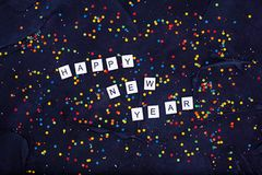Flatlay van Kleurrijk Rond van de Suikergoedconfettien en tekst Gelukkig Nieuwjaar op Zwarte Achtergrond Royalty-vrije Stock Afbeeldingen