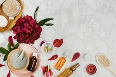 Flatlay of various beauty, bath and SPA products serum, clay, essential oils, body brush, cream etc. And peony flower and petals on a marble background royalty free stock photo