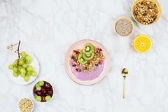 Flatlay of vegan breakfast with plant based yogurt topped with kiwi slices, granola, chia seeds and various fruits royalty free stock images