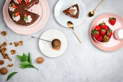 Flatlay with vegan chocolate cake, strawberries, walnuts, cocoa and other dessert ingredients