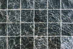 Flatlay of water surface in a pool with dark stone tiles. Holiday concept stock photo