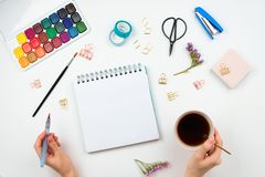 Watercolors, brushes, sketchbook with blank page, woman`s hand holding cup of tea and brushpen and other stationary supplies. royalty free stock photo