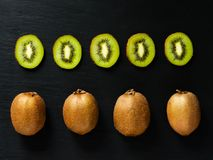 Flatlay with whole and sliced kiwi on black rustic background. Geometrical flat lay with green exotic fresh fruits stock photo