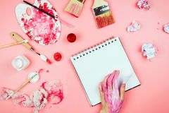 Flatlay with woman`s hands covered in paint, brushes, sketchbook and palette and other artist`s supplies royalty free stock photo