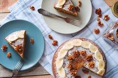 Flatlay z pokrojonym banana tortem z i szklanym słojem dokrętki sproszkowanym cukierem i orzechem włoskim na talerzu z rozwidleni obraz royalty free