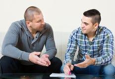 Flatmates discussing tenancy. Adult flatmates discussing tenancy agreement at new apartment Stock Photos