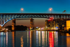 Flats East Bank in Cleveland. CLEVELAND, OH - JUNE 17 2016: The east bank of the Cuyahoga, under highway and railroad bridges, glows with the lights of a new Stock Image