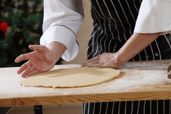 Flatten the dough. Chef sdjusting and flatten the dough Royalty Free Stock Image