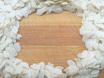 Flattened rice frame on wooden background Stock Photo