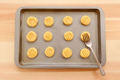 Flattening balls of biscuit dough on a tray Stock Photography