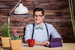 Flattered Woman at Desk. Flattered dapper woman with bowtie at desk with a red coffee cup Stock Image