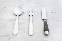 Flatware που τίθεται από το μαχαίρι, δίκρανο, κουτάλι στο σκυρόδεμα Στοκ Εικόνα