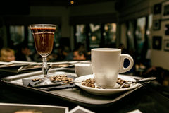 Flatware with coffee glasses and coffee beans in evening cafe. Toned image Stock Photos