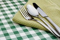 Flatware on green Gingham table cloth. Knife, fork and spoon on a green serviette with a gingham background popular symbol for restaurants Stock Photo