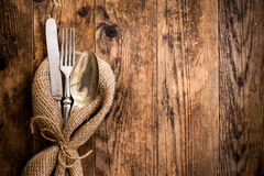 Flatware the old wooden table with a rustic style. The old wooden table cutlery on the burlap Royalty Free Stock Image