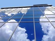 Flaumige weiße Wolken, die von einem Glasgebäude sich reflektieren stockfoto