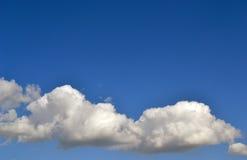 Flaumige Wolken in einem klaren Himmel Stockfoto