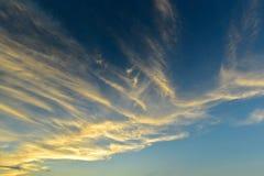 Flaumige Wolken mit Sonnenlichteffekt auf blauen Himmel Lizenzfreie Stockbilder