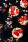 Flaumiger Buttermilchkekse Shortcake mit roten reifen Erdbeeren und frischer Schlagsahne auf einem schwarzen Hintergrund Lizenzfreies Stockfoto
