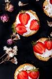 Flaumiger Buttermilchkekse Shortcake mit roten reifen Erdbeeren und frischer Schlagsahne auf einem schwarzen Hintergrund Lizenzfreies Stockbild