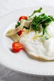 Flaumiges Eiweiß-Omelett mit rukola, Käse- und Kirschtomaten Weißer Teller Ohne Eigelb Stockfoto