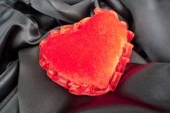 Flaumiges Innerkissen des Valentinsgrußes über schwarzem Satin lizenzfreies stockfoto