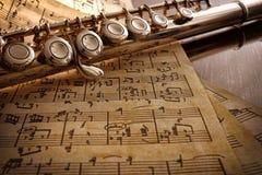 Flauta e partitura escrita à mão velha na tabela preta elevado fotografia de stock royalty free