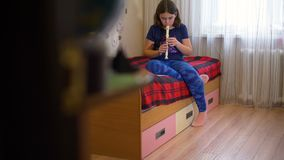 Flauta practicante de la muchacha en su cama por la tarde almacen de metraje de vídeo