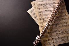 Flauta transversal e partitura velha na opinião de tampo da mesa preta fotografia de stock royalty free